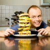 Happy young man is going to eat big layered cheeseburger.jpg