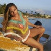Beautiful young Hispanic woman sitting on colorful fishing boat on beach in Negril, Jamaica on sunny day.jpg