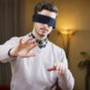 Blindfolded young man at home in living room cannot see, trying to find his way with his hands.jpg