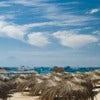 Straw umbrellas and boats on sunny beach resort.jpg