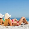 Attractive women in bikinis sunbathing on the beach.jpg