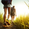 Hikers with backpacks walking through a meadow with lush grass.jpg