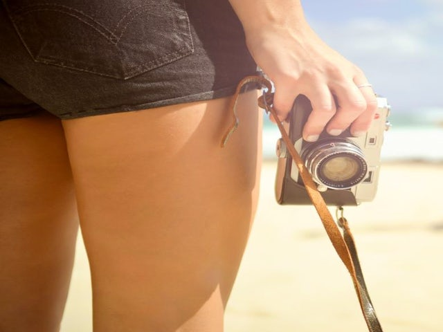 woman-standing-on-beach-and-holding-camera.jpg